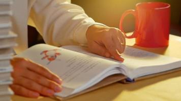 Cerca de la mano de una mujer joven leyendo un libro video