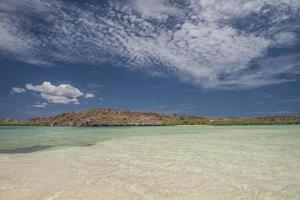 Clear seawater with mountains on the background and blue sky with clouds in the Baja peninsula, Baja California photo