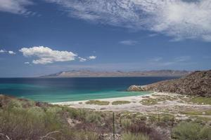 Blue sea with mountains and blue sky with clouds in the Baja peninsula Baja California Sur Punta Armenta, Mexico photo