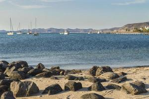 Malecon of La Paz by the sea of Cortes with rocks on the beach and a view of the city with ships on the sea photo