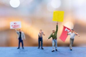 Miniature people, protesters holding signs, raising their hands for revolution photo