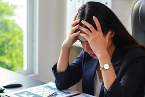 empresaria asiática sentada en la oficina con estrés, las mujeres no son felices en el trabajo. foto