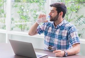 joven empresario está bebiendo un calmante para la sed en casa y trabajando en una computadora portátil. concepto de trabajar y hacer negocios en línea foto