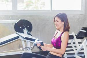 Beautiful Asian woman exercising in the gym photo