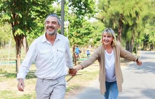 Pareja de ancianos caucásicos caminando de la mano en un parque con amor. concepto de vivir unas felices vacaciones foto