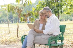 Caucasian elderly couple sits and relaxes on a bench in the park and uses a laptop. Concept of living life happily on the holiday photo
