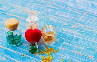 Fish oil in a glass bottle placed on a wooden floor and a red heart with copy space. Medical and health care concepts photo