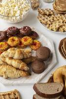 Pastries and snacks on white table cloth photo