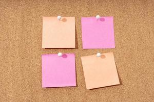 Group of four blank notes on a cork board for adding text and push pin. Mock up photo