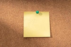 Cork board with blank yellow note for adding text photo
