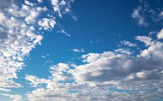 Blue sky with bright clouds background photo