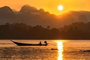 silhouette image of a  boat sailing in a dam in southern of Thailand in the morning. photo