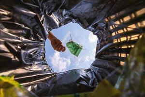 paquete de mascarilla con cierre de cremallera antes de tirarlo a la basura. con una vista de gusano desde el interior de la papelera. foto