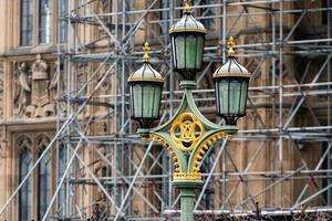 Street lamps on Westminster Bridge, bloored Westminster Abbey on background, London, UK photo