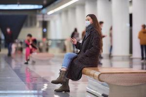 una mujer con una mascarilla médica está esperando un tren y sosteniendo un teléfono inteligente foto