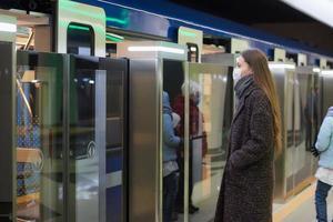 una niña con una mascarilla quirúrgica mantiene la distancia social en una estación de metro foto