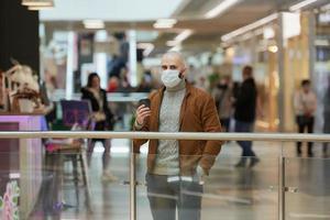 un hombre con una mascarilla está sosteniendo una taza de café en el centro comercial foto