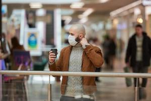 un hombre se pone una máscara mientras sostiene una taza de café en el centro comercial foto