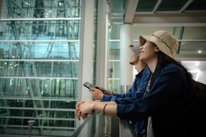 traveler couple person travel at aerodrome with baggage, journey vacation trip with man and woman, flight transportation arrival waiting in airport terminal photo