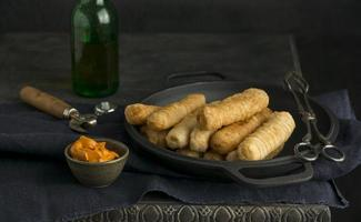 Composition with traditional tequenos on a plate photo