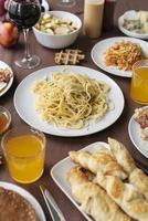 Pasta, bread, and snacks on table photo