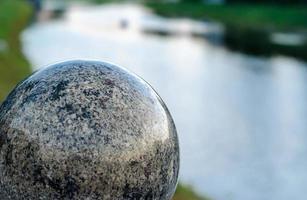 Gran bola de mármol decorativa con el fondo del río. foto