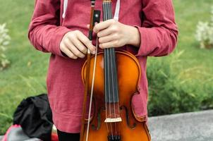 Hands of a street musician girl with violin photo