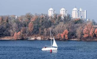 Yacht with a white sail on the background of the coast and the city photo