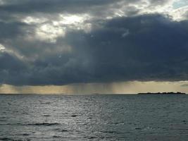 Huge black cloud pours rain on the sea photo