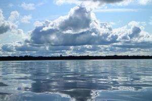 Cumulus clouds reflected in the sea photo