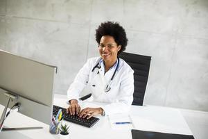 doctor sonriendo mientras trabaja en una computadora foto