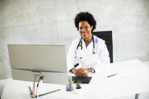 doctor sonriendo y trabajando en una computadora foto
