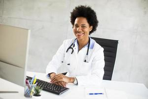 Doctor behind a computer smiling photo