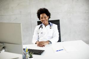 Doctor wearing white coat behind desk in office photo