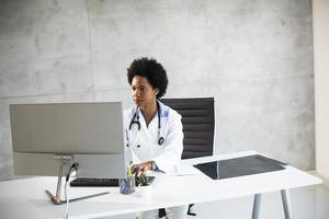 Doctor in a white coat behind a desk in an office photo