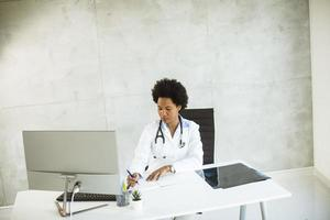 Doctor taking notes behind a desk photo