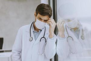 Doctor in mask leaning against a window photo