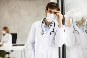 Doctor looking worried while wearing a mask photo