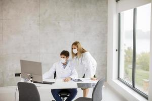 Two doctors working at a computer while wearing masks photo