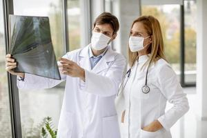 Two doctors in masks looking at an x-ray photo