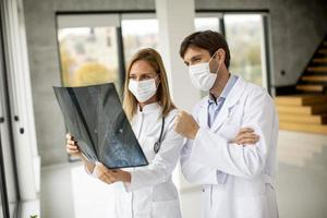 Two masked doctors examining an x-ray photo