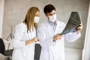 Close-up de médicos enmascarados mirando una radiografía foto