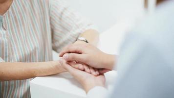 Cerca de un médico de la mano de un paciente mayor video