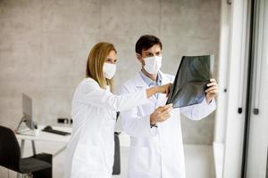 médicos enmascarados mirando una radiografía foto