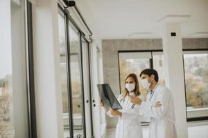médicos enmascarados con una radiografía foto