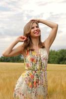 Happy woman in a dress in a field photo