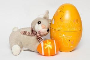 Huevos de plástico amarillos y naranjas con un conejo de peluche, que se utilizan para la decoración de Pascua. foto