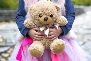 niña sostiene su osito de peluche foto