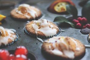 muffins de naranja y cereza en un molde para hornear muffins foto