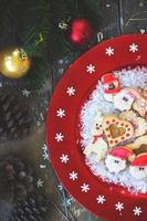 Christmas cookies on red festive plate with snowflakes photo